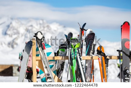 Photo of multi-colored skis in snow at winter resort in afternoon. #1222464478