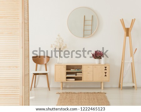 Wooden cabinet with flowers and heather between stylish brown chair and wooden hanger, real photo #1222465123
