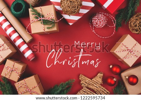 Christmas greeting card. Background with gift boxes, clews of rope, paper's rools and decorations on red. Preparation for holidays. Top view. #1222595734