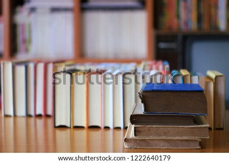Close-up of old books stacked in library many books stacked in the background selective focus and shallow depth of field #1222640179