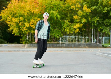 Full length portrait of contemporary young man riding skateboard outdoors in extreme park, copy space #1222647466