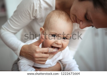 Mom helps to brush the teeth of a happy baby, Hygiene of the baby's mouth, brushes her teeth with a special nozzle. #1222671664