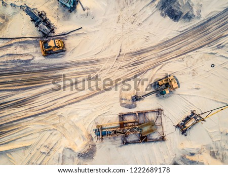 Aerial view of machinery and mine equipment near road on sandy surface Royalty-Free Stock Photo #1222689178