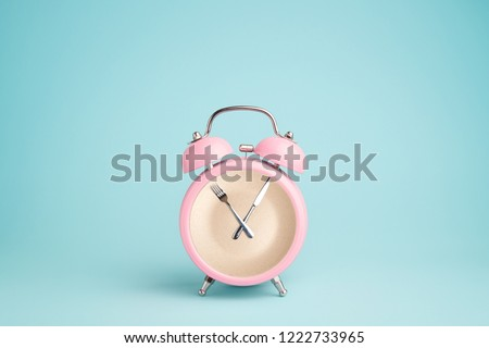 Plate inside the pink alarm clock. Concept of intermittent fasting, lunchtime, diet and weight loss #1222733965