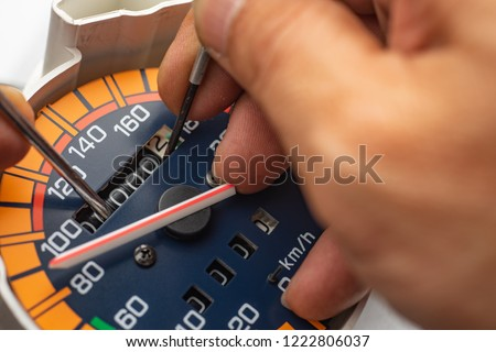 """Odometer Reprogramming """"car clocking"""" hand of technician Modify The speedometer and reset number to zero Royalty-Free Stock Photo #1222806037"""