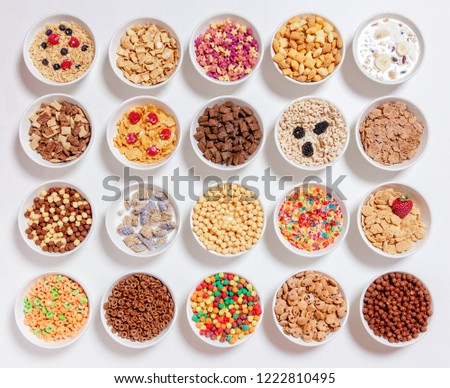 set of different cereals with milk on a white background. 20 bowls with cornflakes, kashi, cereals and berries. the concept of breakfast food. flat lay, top view  #1222810495