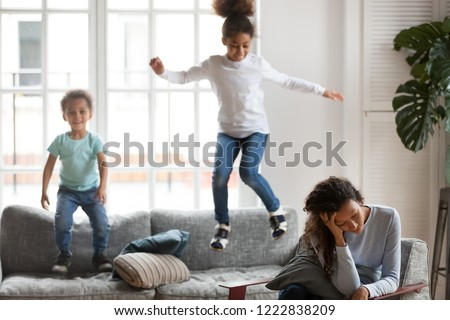Frustrated African American woman having problem with children upbringing, upset single mother hold head in hands, playful son and daughter jump on couch, depression, difficulties with educate kids #1222838209