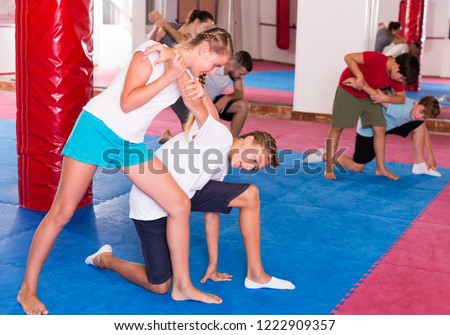 Kids with adults practicing effective techniques of self-defence in training room Royalty-Free Stock Photo #1222909357
