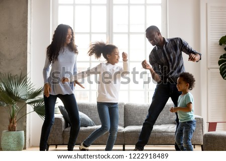 Happy African American having fun together indoors, funny married couple dancing with adorable little preschooler daughter and cute toddler son at home, listening to music, family weekend with kids #1222918489