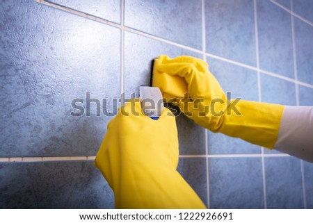 A woman with a rubber yellow glove wipes the tiles in the kitchen with a sponge #1222926691