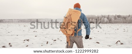 back view of  tourist with  backpack hiking in winter in Norway / one man carrying  backpack in a Norwegian winter landscape. #1222999282