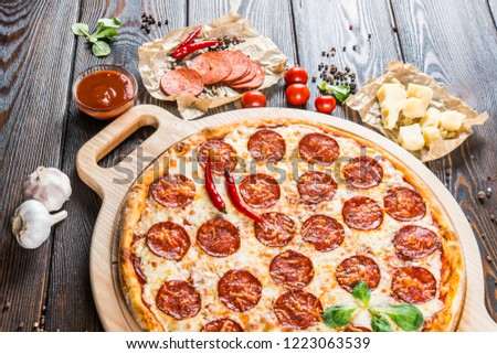 Large spicy pizza with salami and pepperoni sausage on a round cutting board on a dark wooden background. Pizza Ingredients #1223063539