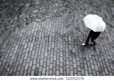 Woman with umbrella in the rain on paving stone road