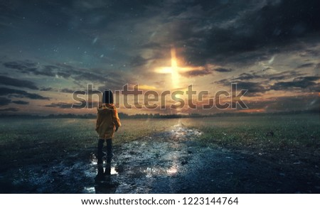 A little girl stands in the rain with a glowing cross in the sky Royalty-Free Stock Photo #1223144764