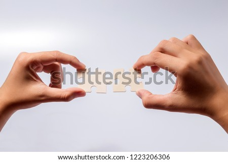 Pieces of jigsaw puzzle in woman's hands #1223206306