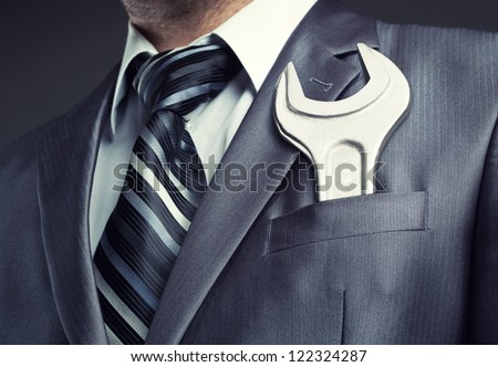 Businessman with spanner in suit pocket #122324287