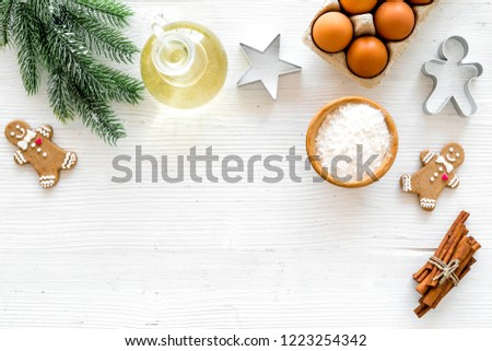 Ingredients for New Year gingerbread cookies. Eggs, flour, cinnamon, oil near gingerbread man and spruce branch on white background top view copy space #1223254342
