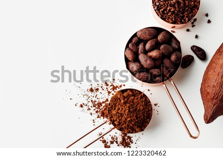 Rose gold measuring cups of cocoa beans, cacao nips, cocoa powder and cocoa pods on a white background, flat lay healthy food concept #1223320462