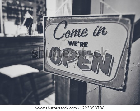 the sign on the front door to the coffee shop. inscription on the plate: Come in, we're open. #1223353786
