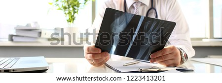 Male doctor hold in arm silver pen and look at xray photography closeup. Skeleton bone disease exam medic aid or cancer physical test in hospital for healthy lifestyle education career concept #1223413201