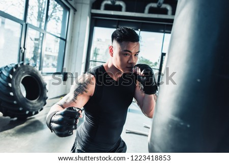 young sportsman wearing boxing gloves and punching boxing bag at gym #1223418853