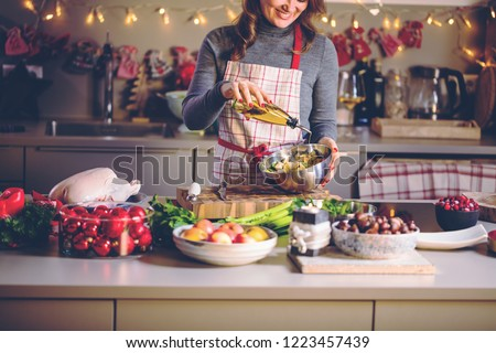 Young Woman Cooking in the kitchen. Healthy Food for Christmas (stuffed duck or Goose) #1223457439