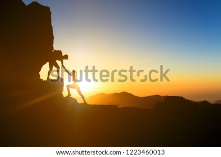 Teamwork couple helping hand trust help silhouette in mountains, sunset. Team of climbers man and woman hikers, help each other on top of mountain, climbing together, inspiring sunset on Gran Canaria #1223460013