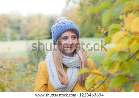 Woman in a yellow coat in a park with autumn leaves #1223463694