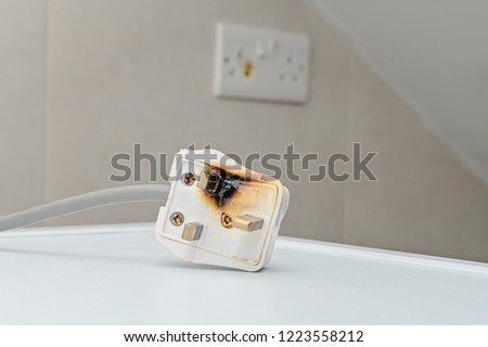 Burned 250V uk style socket and converter. Improper use of AC Power Plugs and Sockets cause of short circuit and fires at home Royalty-Free Stock Photo #1223558212