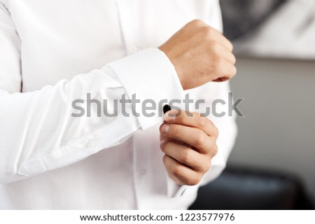 Handsome man, groom buttoning black cufflink on white shirt #1223577976