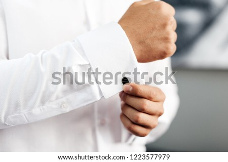 Handsome man, groom buttoning black cufflink on white shirt #1223577979