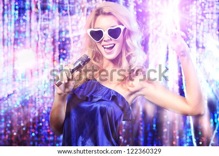 Portrait of a beautiful blonde girl singing with a microphone. Disco lights in the background. Royalty-Free Stock Photo #122360329