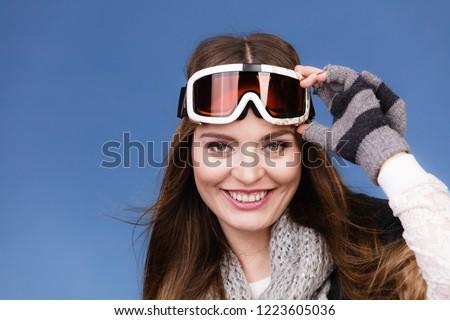 Woman skier girl wearing warm clothing ski googles portrait. Winter sport activity. Beautiful sportswoman on blue studio shot #1223605036