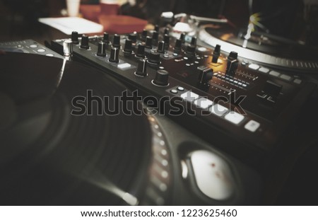 Royalty free image of  hip hop dj setup on stage in night club. Turntable vinyl player device and sound mixer panel.Play and remix music tracks in nightclub.Curated collection of djs musical equipment