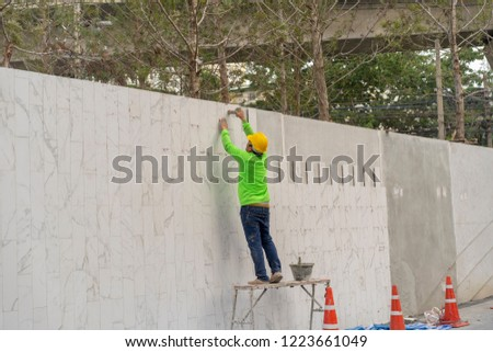 mason worker during installed white gray marble on the wall #1223661049