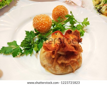 Meat baked in an envelope of pita and cheese balls. Cheese balls in sesame with meat on a white plate. Banquet dish #1223721823