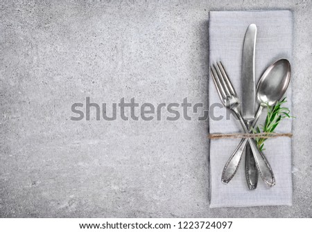 Table setting background with copy space. Concrete background with napkin, silverware and rosemary branch. Cutlery with fork, knife and spoon. Top view. #1223724097