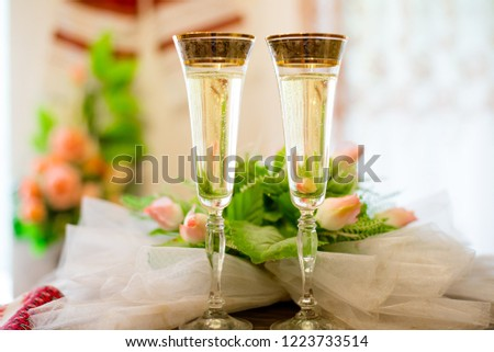Festive glasses of champagne on the background of flowers #1223733514