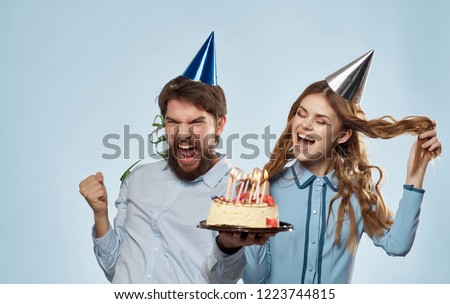man and woman in holiday caps with a cake