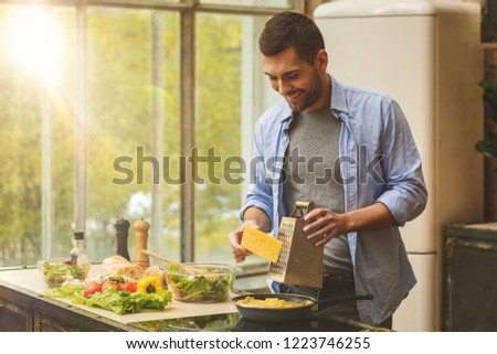 Man preparing delicious and healthy food in the home kitchen on a sunny day.  #1223746255