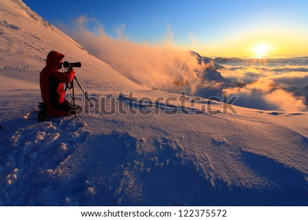 Photographer with the camera on tripod at sunset during winter