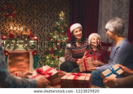 Merry Christmas and Happy Holidays! Grandma, grandpa, mum, dad and child exchanging gifts. Parents and daughter having fun near tree indoors. Loving family with presents in room. #1223829820