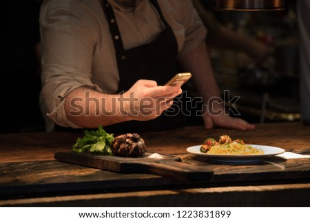 Chef taking pictures of pasta in restaurant kitchen