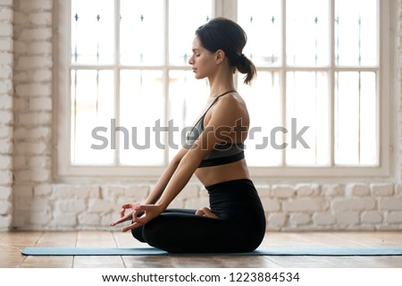 Young sporty attractive woman practicing yoga, doing Ardha Padmasana exercise, Half Lotus pose, working out, wearing sportswear, black pants and top, indoor full length, white yoga studio, side view #1223884534