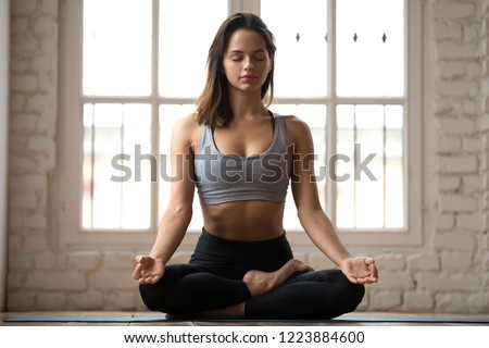 Young sporty attractive woman practicing yoga, doing Ardha Padmasana exercise, meditating in Half Lotus pose with mudra gesture, working out, wearing sportswear, indoor full length, white yoga studio #1223884600