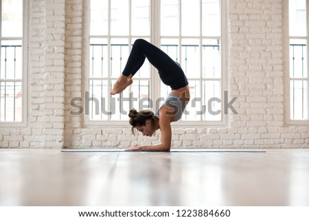 Young sporty attractive woman practicing yoga, doing Vrischikasana, Scorpion exercise, handstand pose, working out, wearing sportswear, pants and top, indoor full length, yoga studio #1223884660