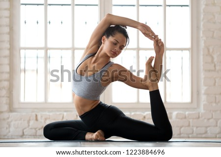 Young sporty attractive woman practicing yoga, doing Mermaid exercise, Eka Pada Rajakapotasana pose, working out, wearing sportswear, pants and top, indoor full length, white yoga studio #1223884696