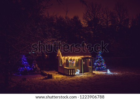 Wooden painted yellow private children`s play house in home garden, decorated with Christmas LED string lights outdoors in cold winder night. Decorated Christmas fir tree. #1223906788