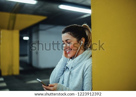 Sportswoman at underground parking using mobile phone #1223912392
