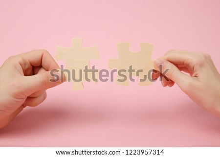 Close up cropped photo of hands holding trying to connect couple wooden jigsaw puzzle pieces isolated on pastel pink wall background. Association, connection concept. Copy space advertising mock up #1223957314